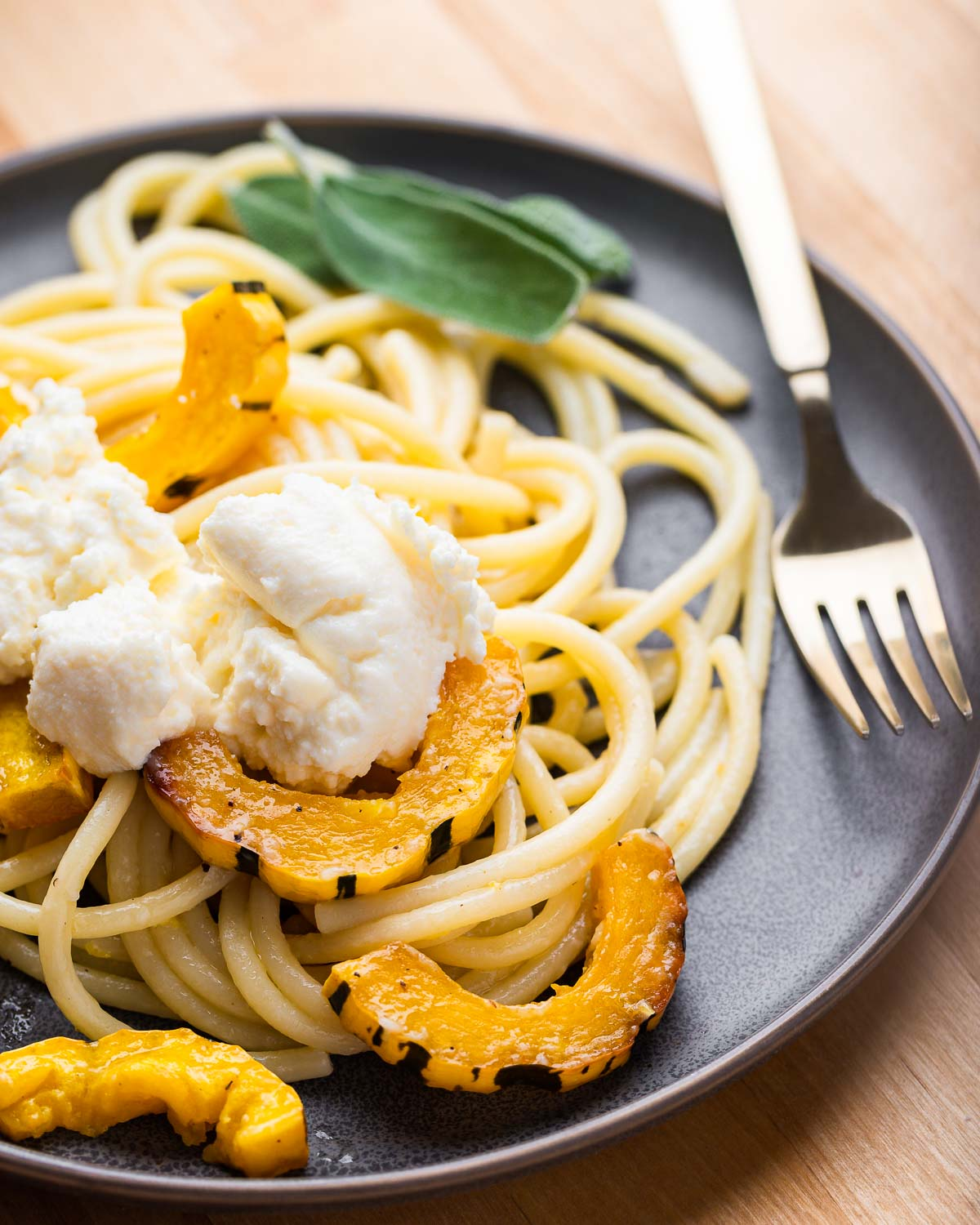 Grey plate with delicata squash bucatini and dollop of ricotta on top.