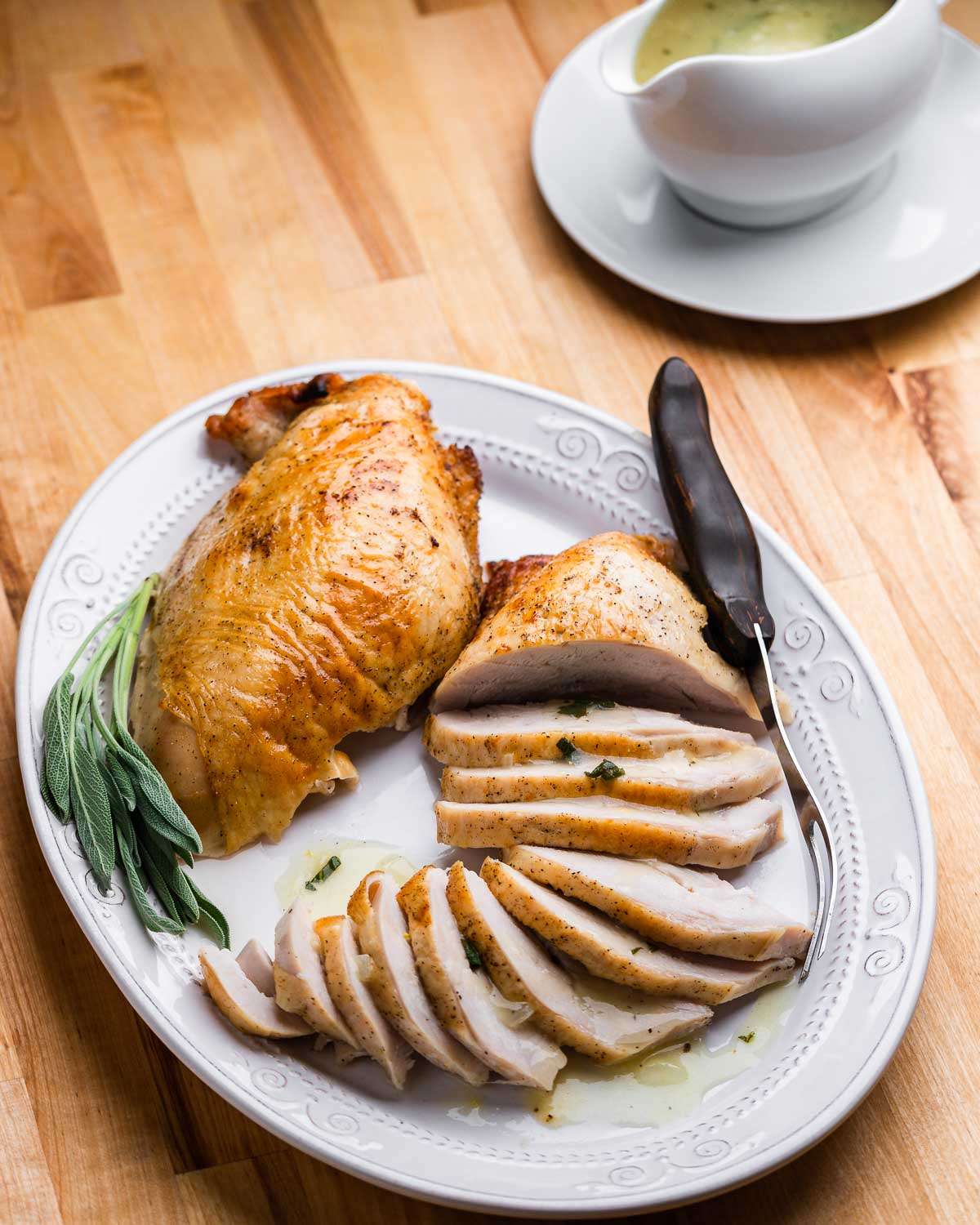 Platter with one carved and one uncarved turkey breast and carving fork.