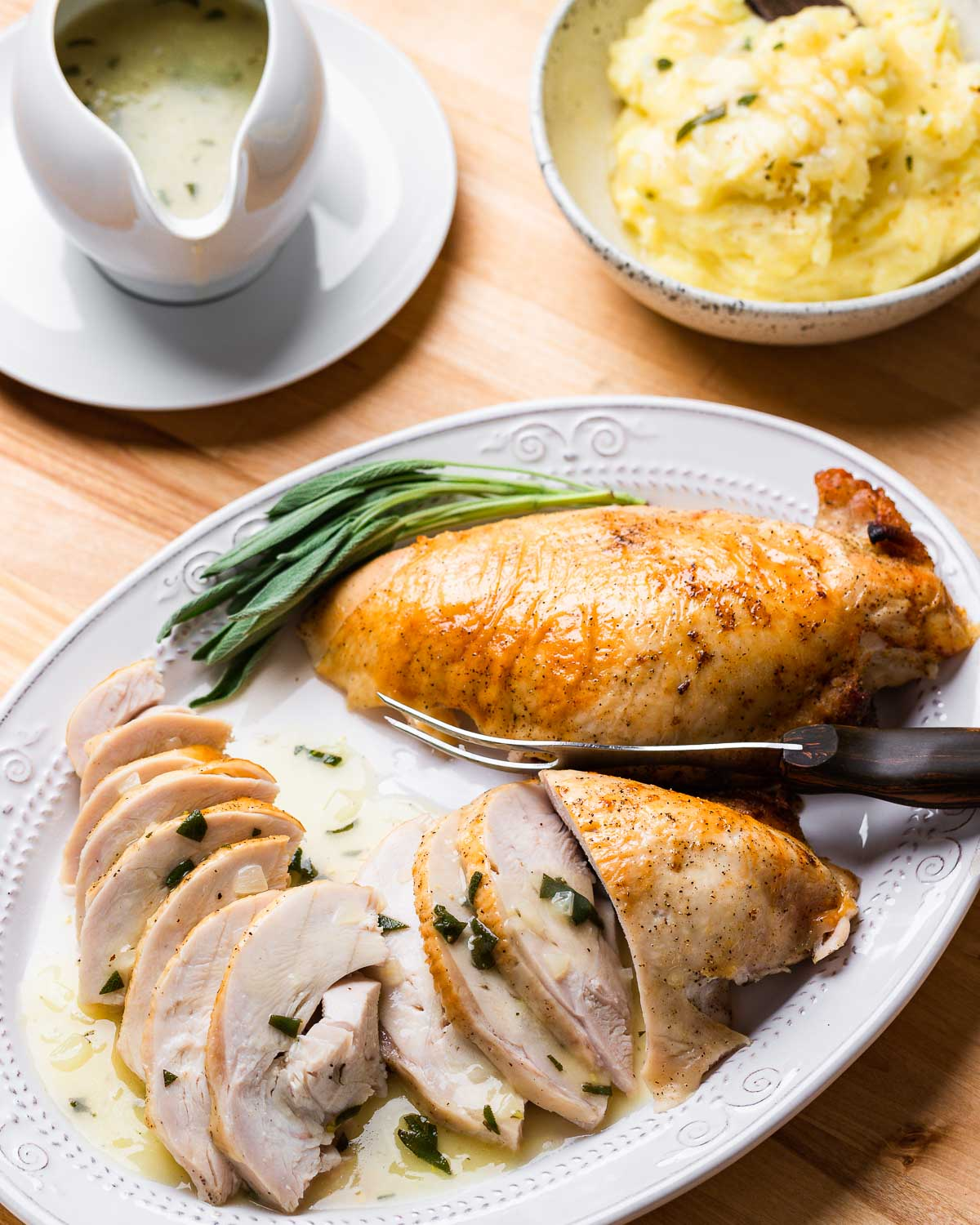 Platter with carved turkey breast, bowl of mashed potatoes, and gravy boat.