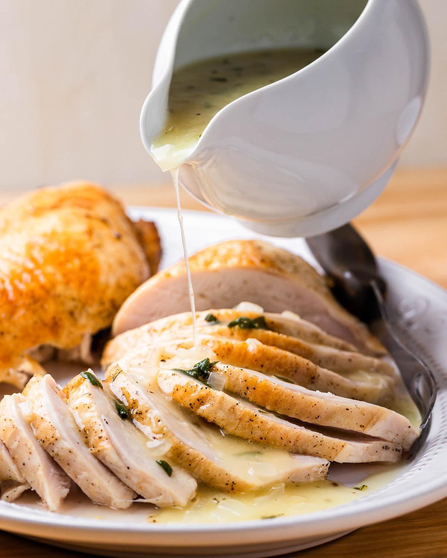 Turkey gravy being poured onto platter of turkey.