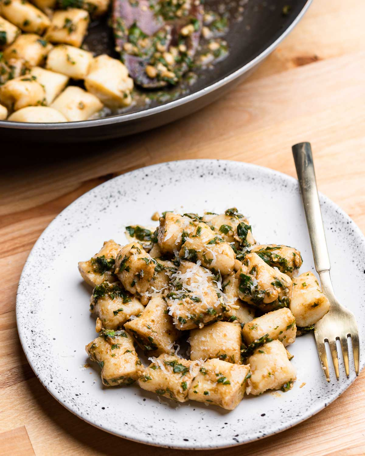 Gnocchi in white plate with brown butter and pesto.