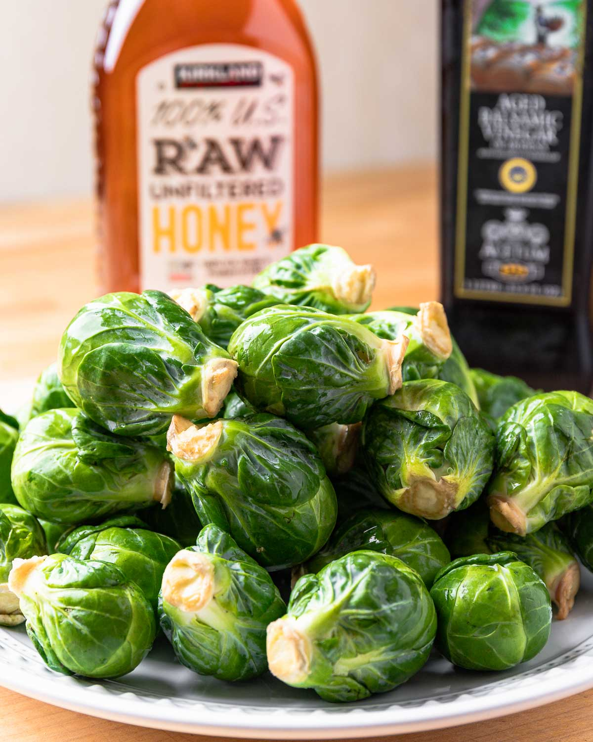 Ingredients shown: honey, balsamic vinegar, and plate of brussels sprouts.