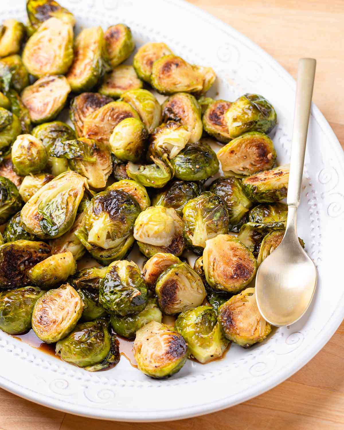 Plate of honey balsamic brussels sprouts in white plate with gold spoon.