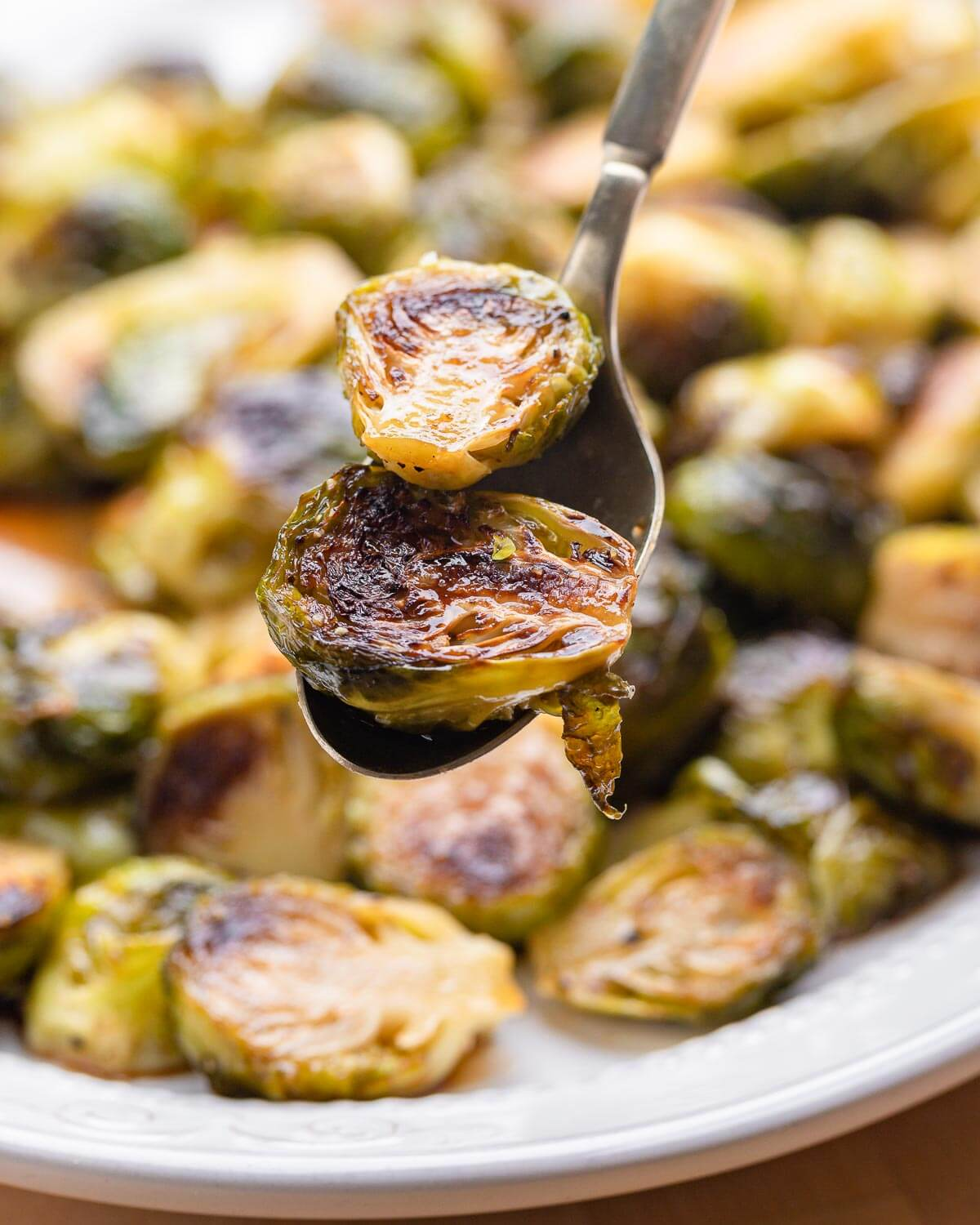 Spoon holding 2 pieces of roasted brussels sprouts.
