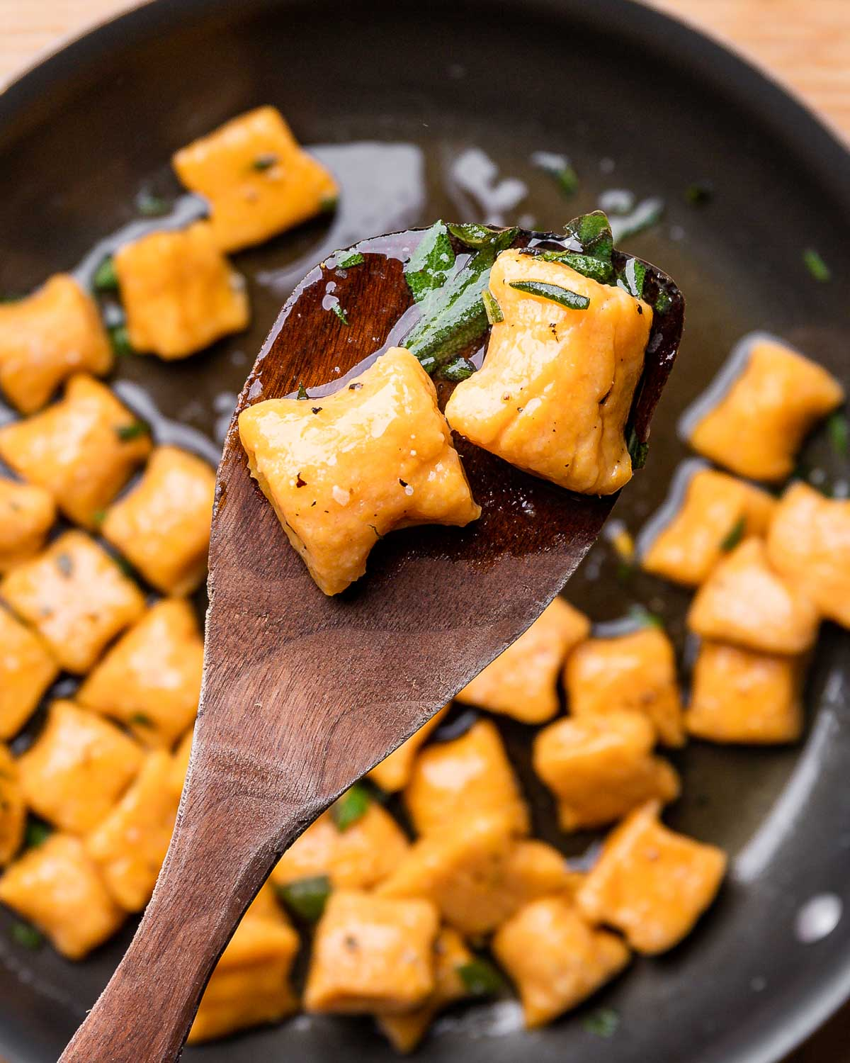 Wooden spoon holding 2 cooked sweet potato gnocchi.