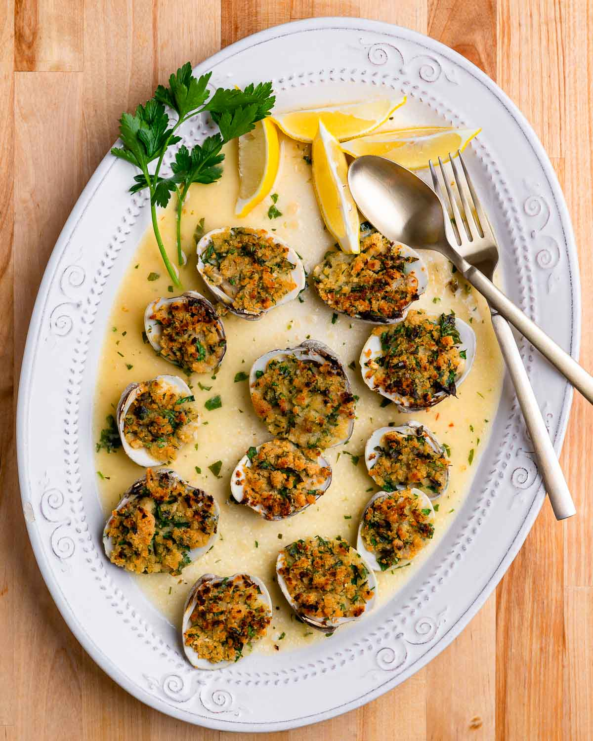 Overhead shot of cooked clams oreganata in oval plate.