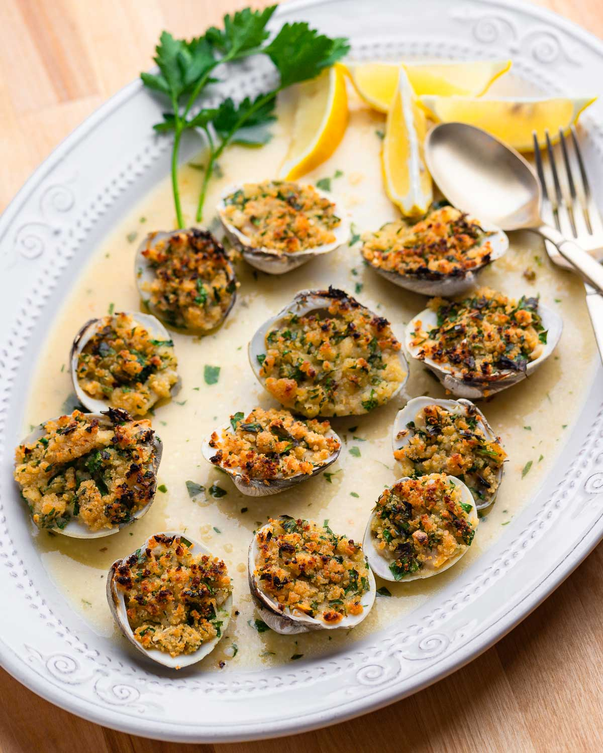 Full plate of cooked clams oreganata on wood table.