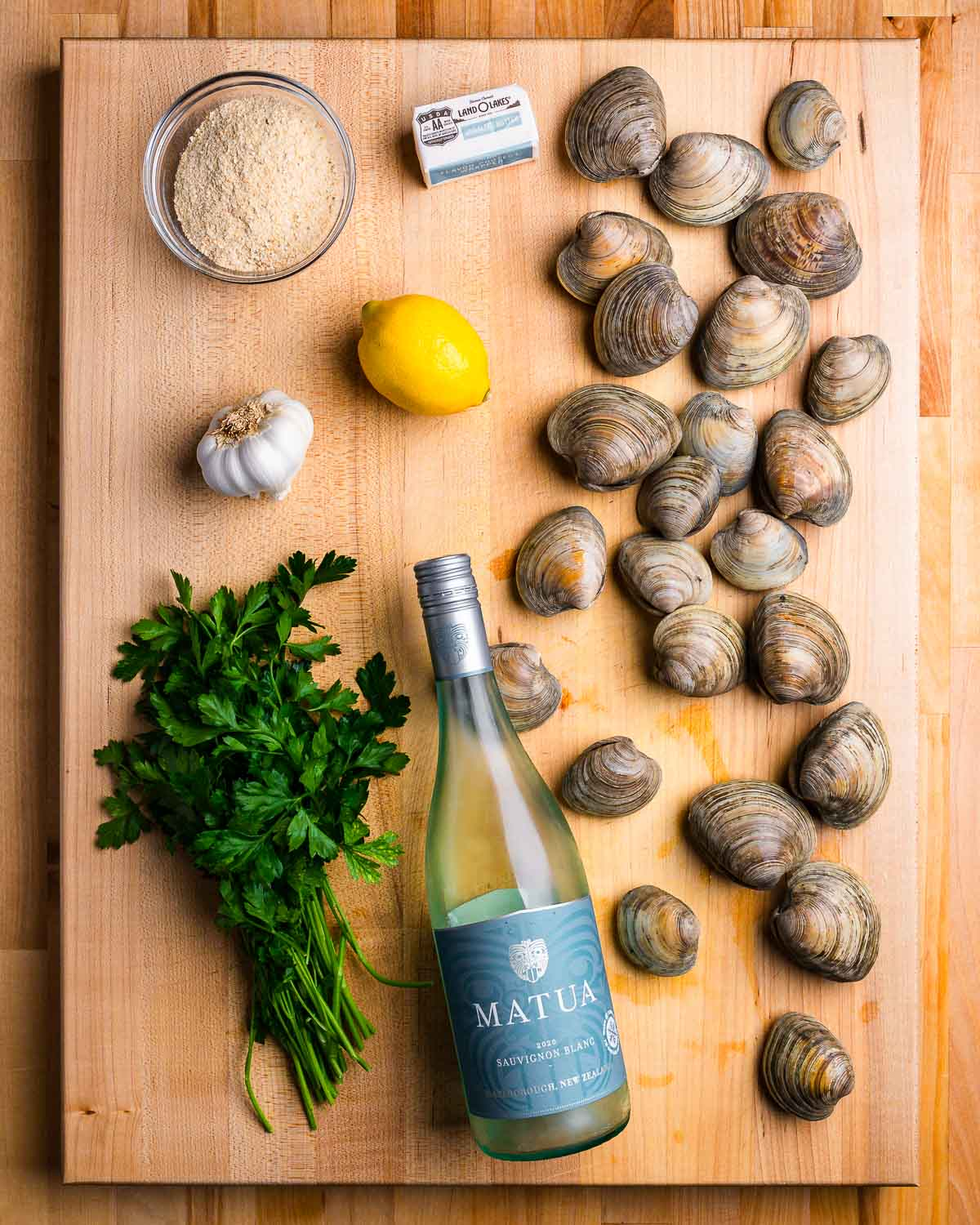 Ingredients shown: breadcrumbs, butter, Littleneck clams, lemon, garlic, parsley, and white wine.