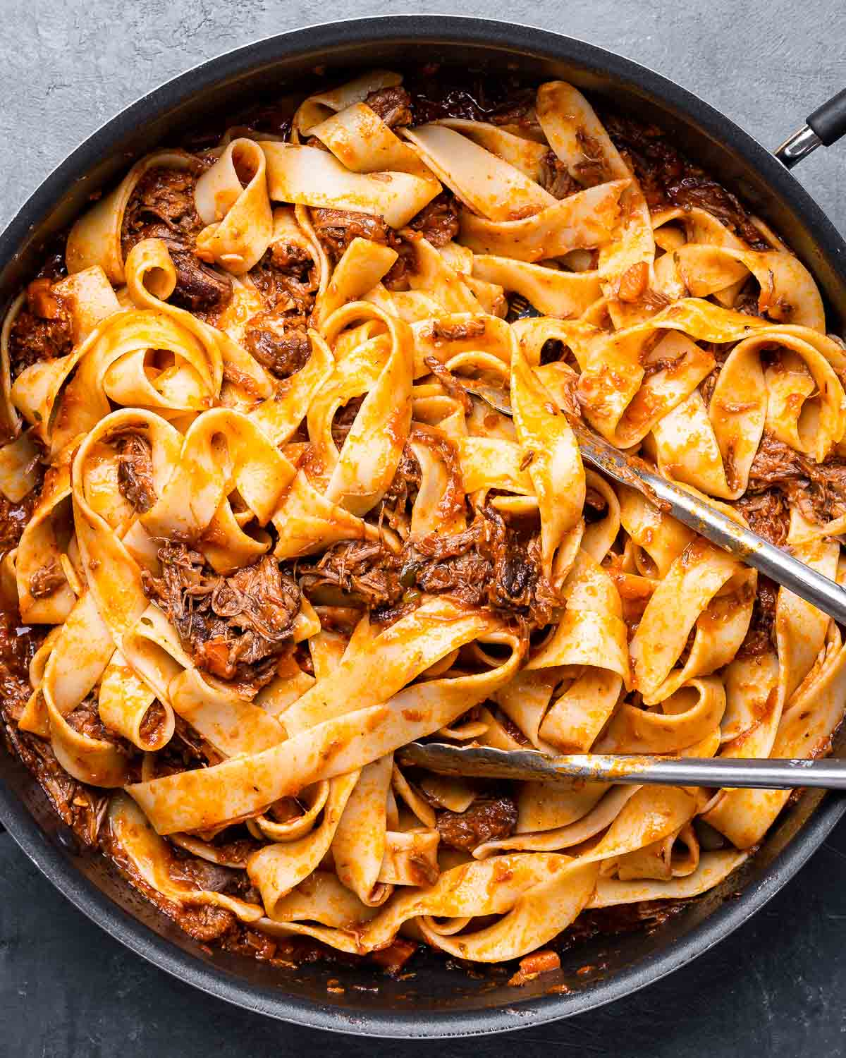 Large pan of pappardelle pasta with short rib ragu.