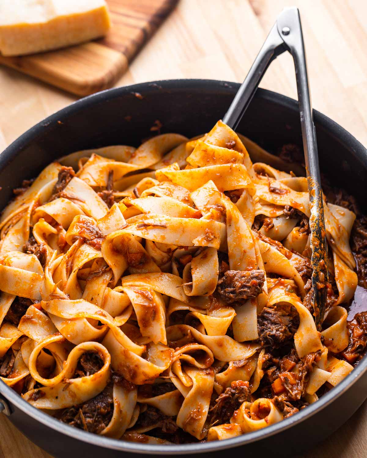 Large pan with short rib pappardelle on wood table.