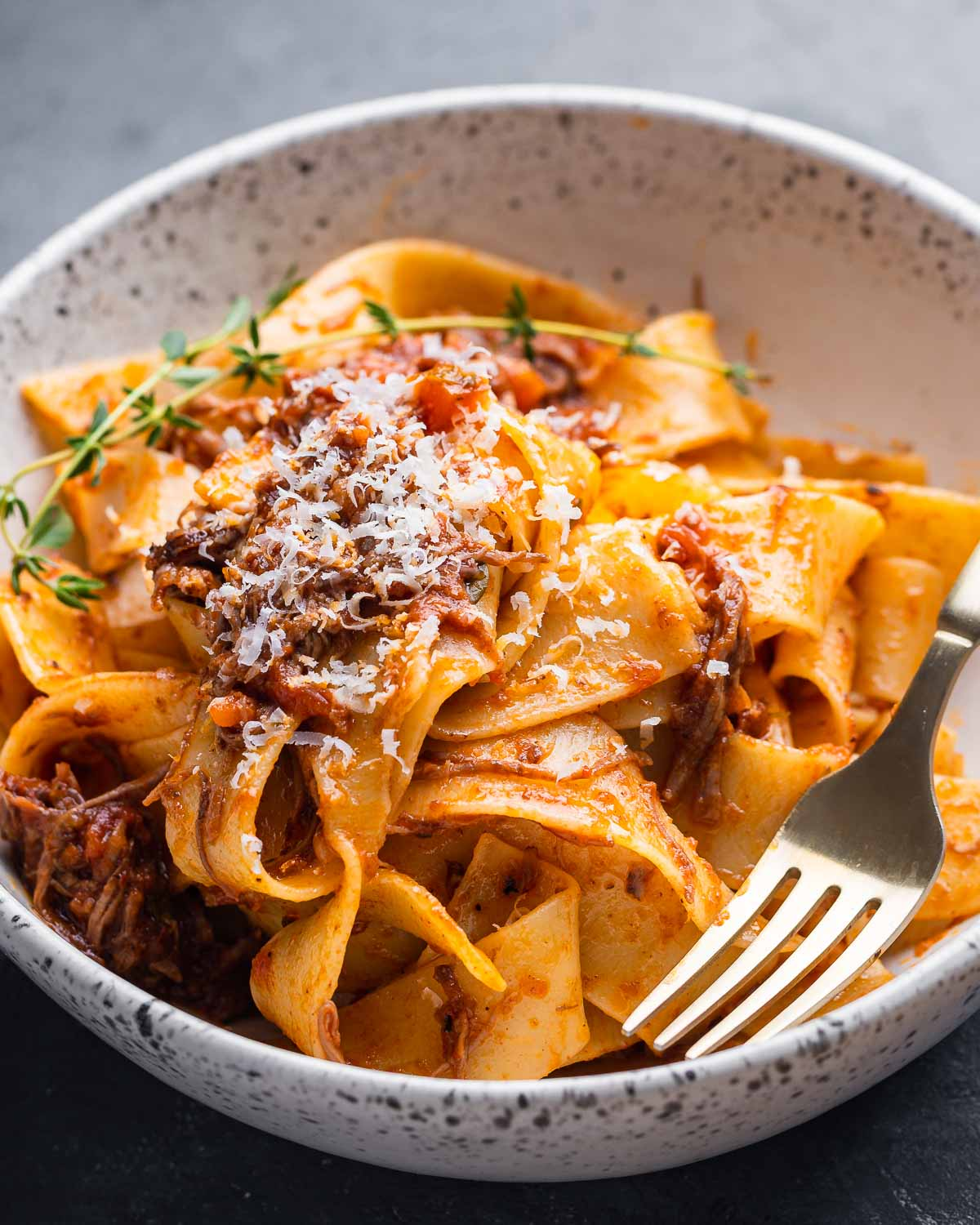 White bowl with short rib ragu over pappardelle.